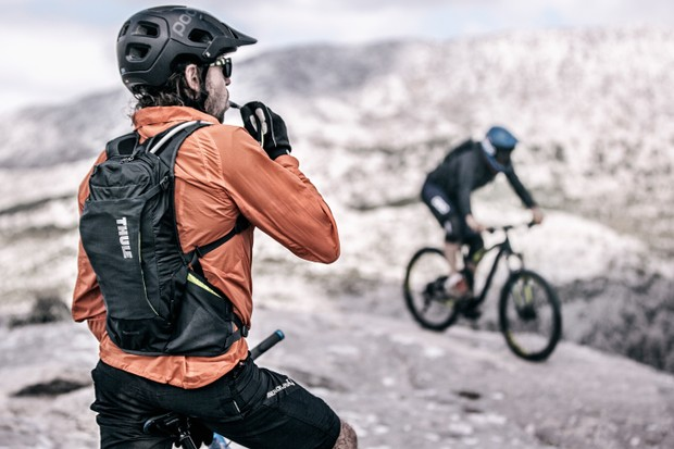man on mtb drinking from hydration backpack